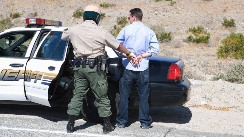 Policeman arresting criminal on road.