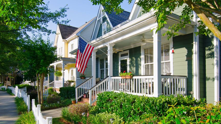 Fort Mill, South Carolina, USA - June 6, 2014: The American Dream is pictured in this iconic image of a row of new, Victorian-style homes with a white picket fence in the Baxter Village neighborhood development located south of Charlotte, North Carolina.