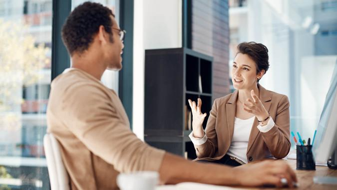 two businesspeople having a discussion in an office.