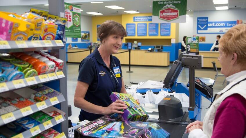 Walmart associate helping checkout customer