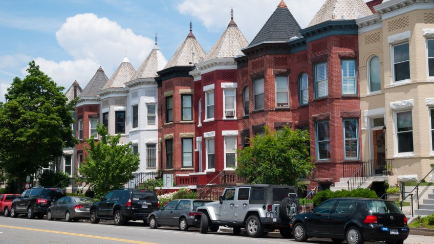Cars are parked in front of rowhouses in a Washington DC neighborhood.