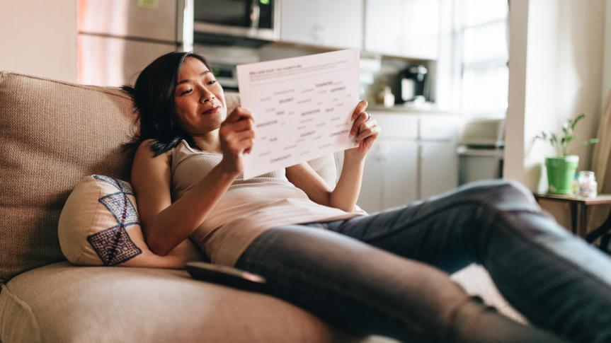 woman reading the papers at home on the couch.