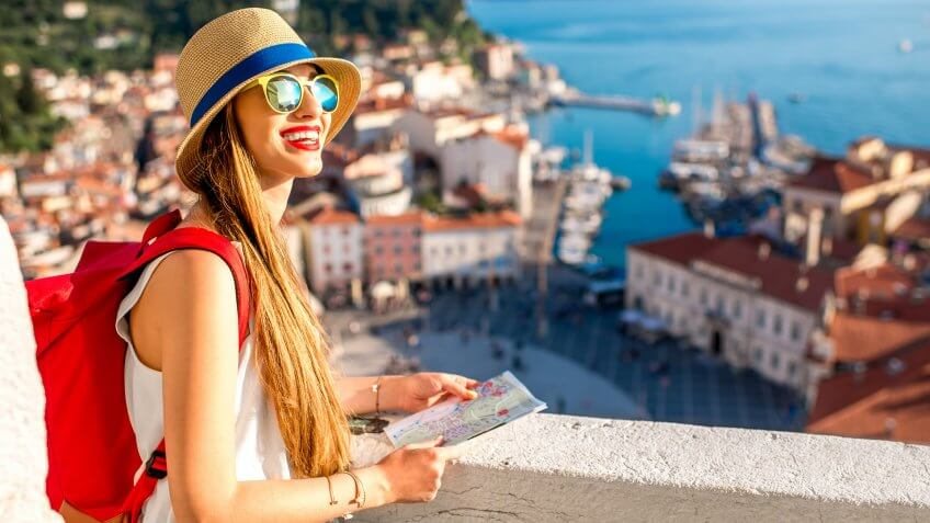 Young female traveler with red backpack and hat enjoying the view from George's tower on Piran old town.