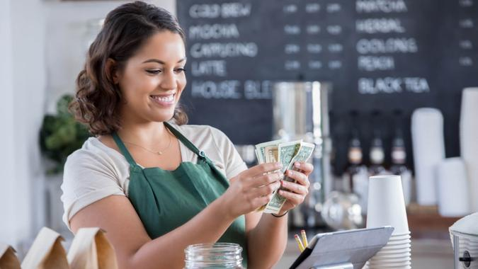 A smiling young female barista stands at the counter in her coffee shop and looks down as she counts paper bills that she has just pulled from her tips jar.