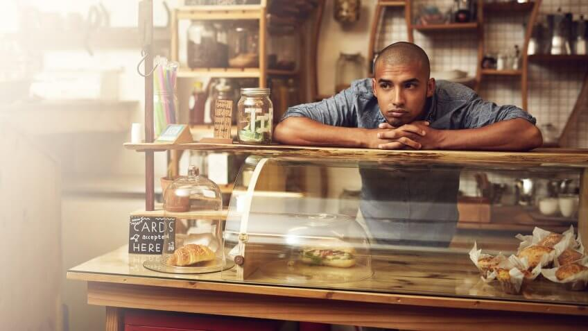 Shot of a young man standing behind the counter of his store and looking downhearted.