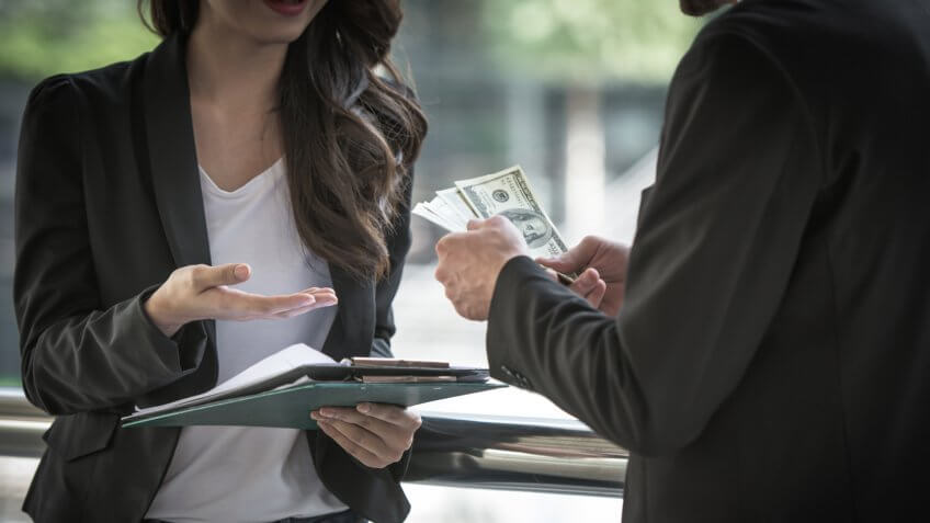 Businessman as an employer paying cash in US dollar bills, wage, loan and bribery concepts.