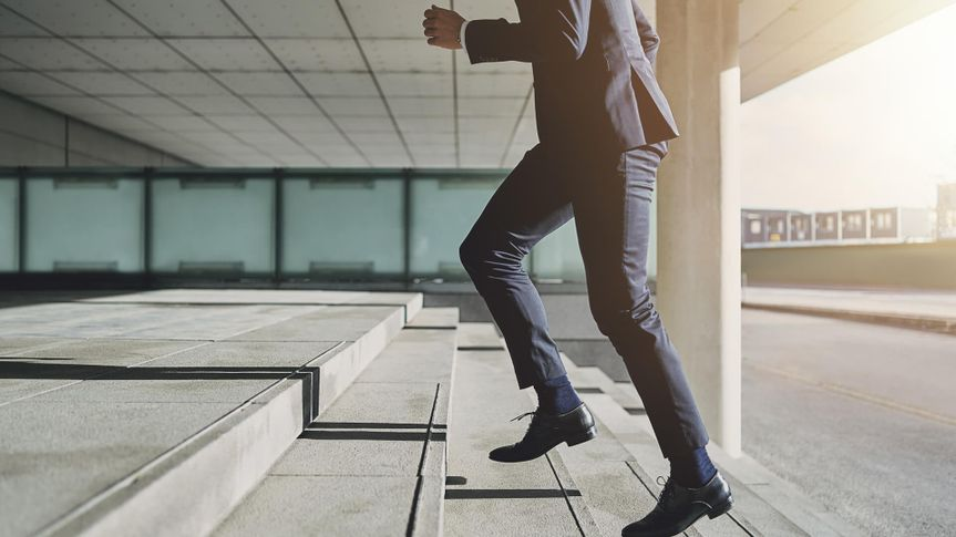 Businessman running fast upstairs.