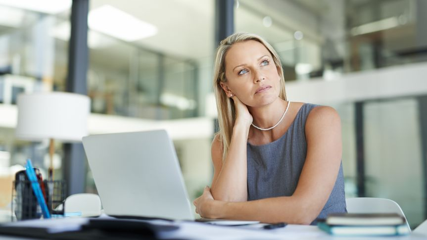 Shot of a mature businesswoman using a laptop in a modern office and looking thoughtful.