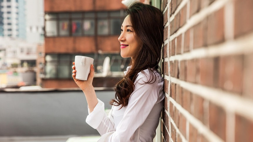 Young business woman having a break drinking an hot coffee on the rooftop of his office building in downtown Seoul, South Korea.