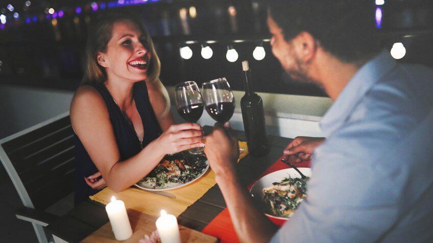 Beautiful couple in love having romantic dinner at night.