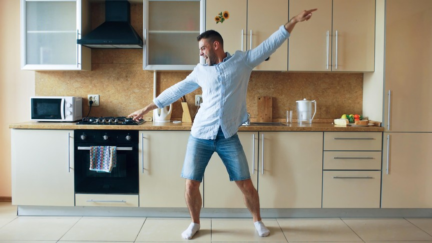 Handsome young funny man dancing in kitchen at home in the morning and have fun on vacation.