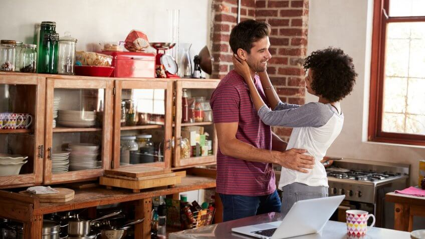 Young mixed race couple embracing in kitchen, waist up.