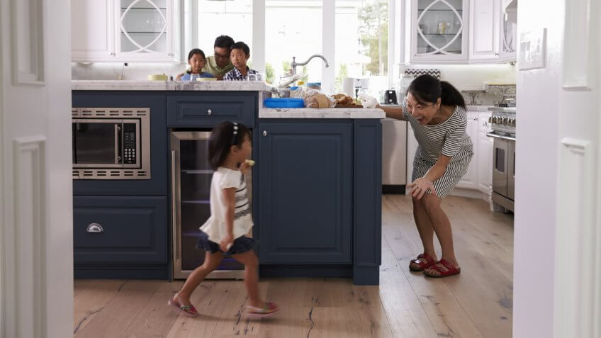 Parents Prepare Food As Children Play In Kitchen.