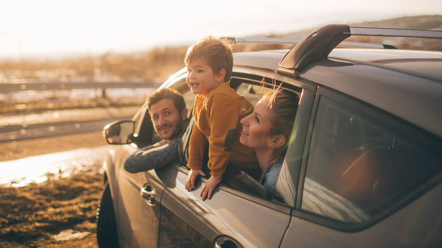 Photo of cute little family during their excursion with family car.
