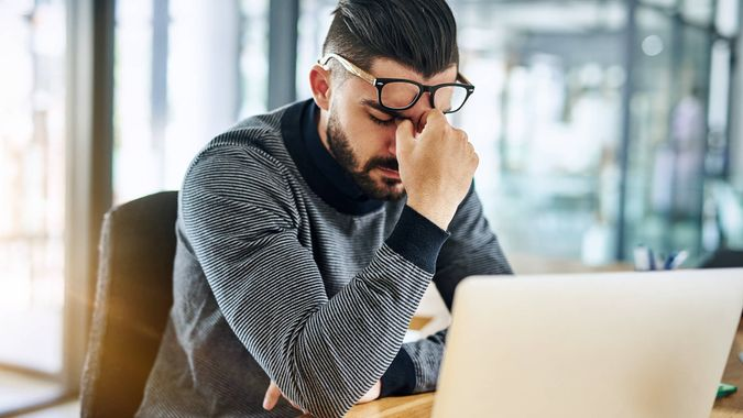 Shot of a young designer looking stressed out while working in an office.