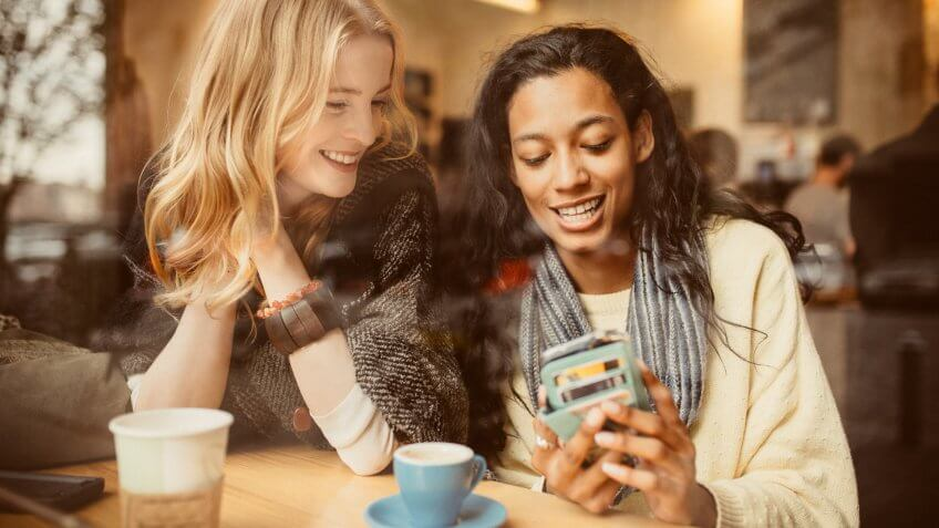 Girlfriends using Smartphone in Coffeeshop.