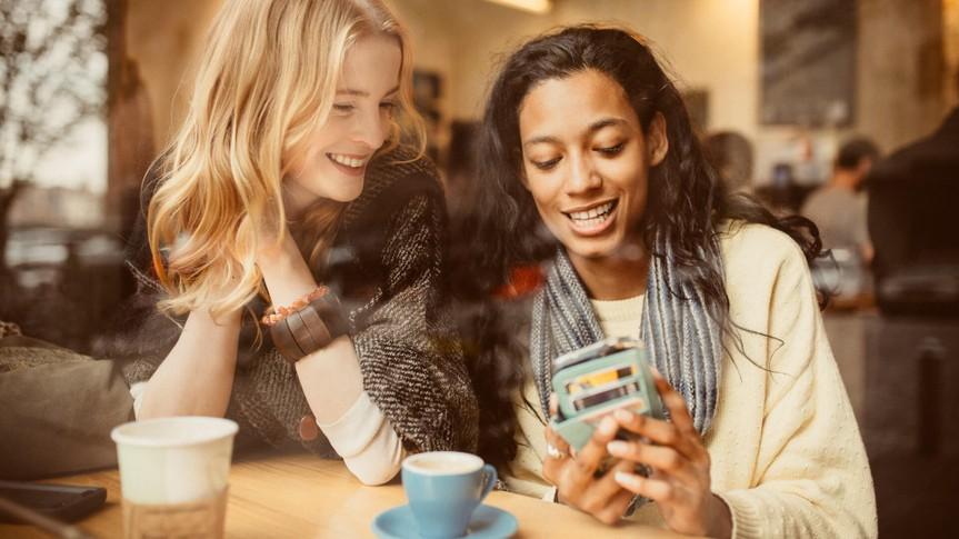 Girlfriends using Smartphone in Coffeeshop.