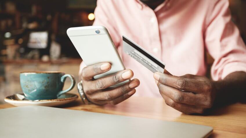 guy holding credit card with iPhone