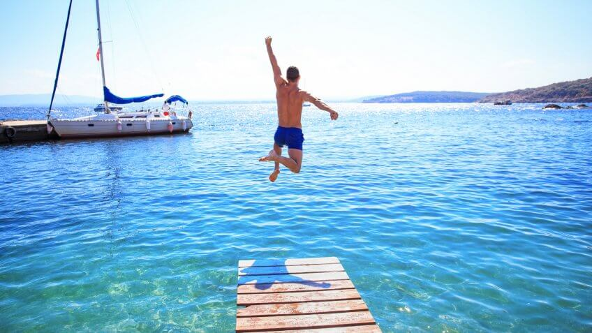 Young man jumping into water from a pier.