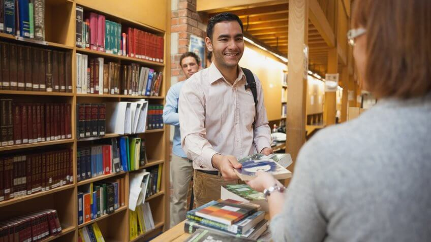 Mature female librarian handing a book to young man in library.