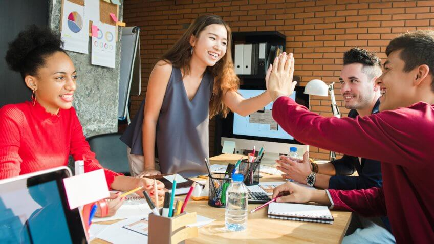 Casual business people making high five in the meeting - business celebration concept.