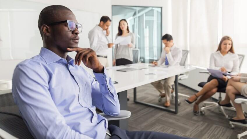 Businessman thinking during meeting in office.