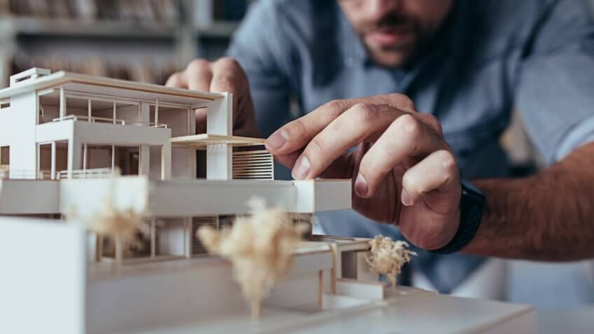 Close up of male architect hands making model house.