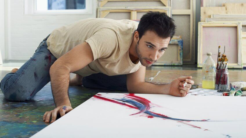 male fine artist painting in studio