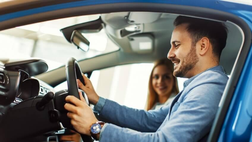 Young couple choosing new car for buying in dealership shop.