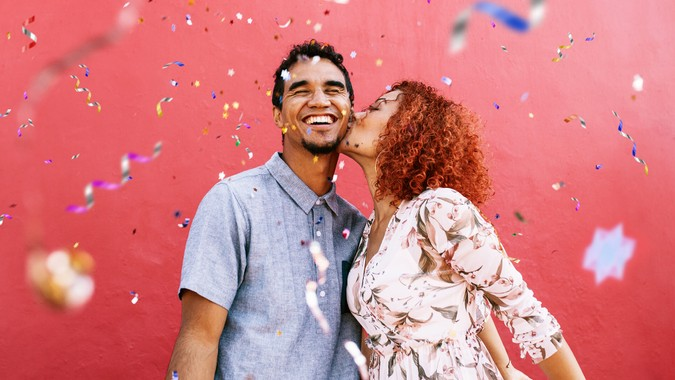 Young woman kissing man on cheek with confetti falling all around them.