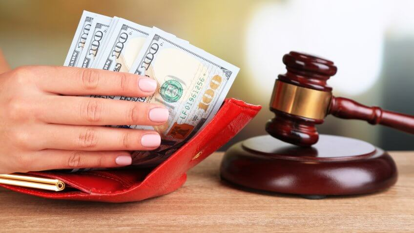 Gavel and hand holding money in wallet on wooden background.