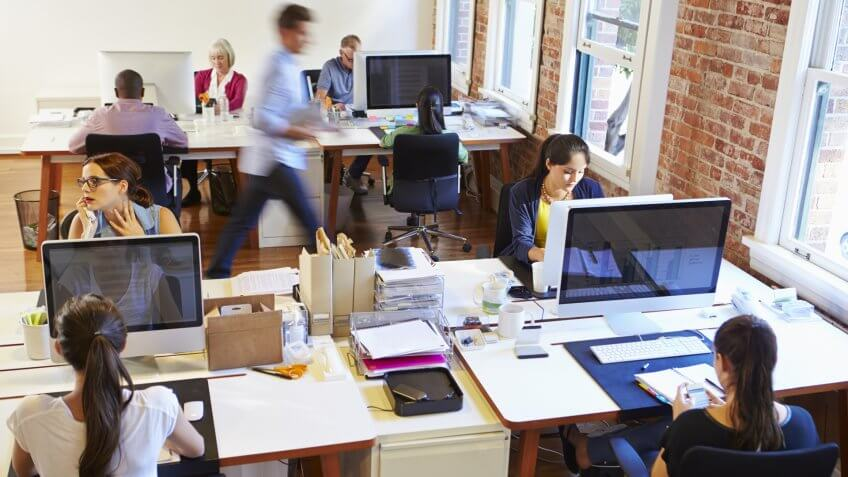 Wide Angle View Of Busy Design Office With Workers At Desks.