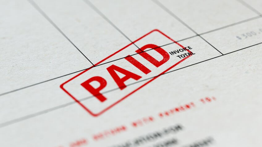 Close-up picture of an invoice with red paid stamp with selective focus.