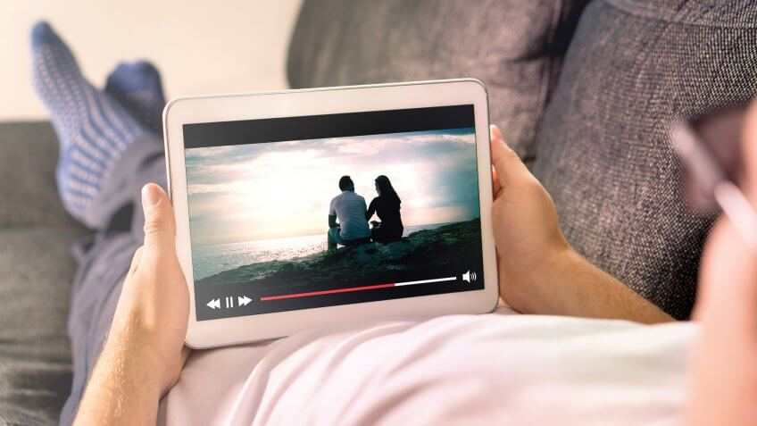 person streaming movie on tablet