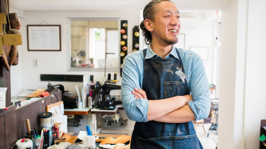 Portrait of a craftsman wearing an apron looking away from the camera.