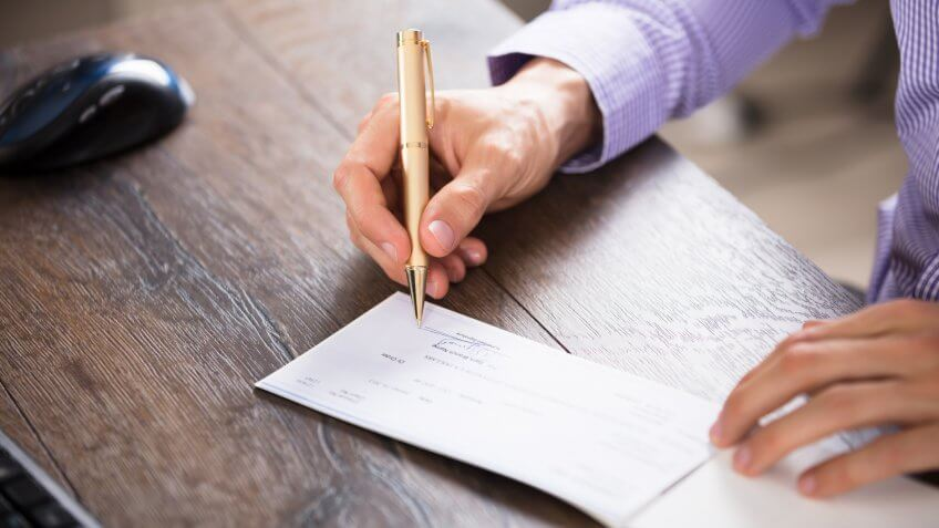 Close-up Of A Businessperson's Hand Signing Cheque In Office.