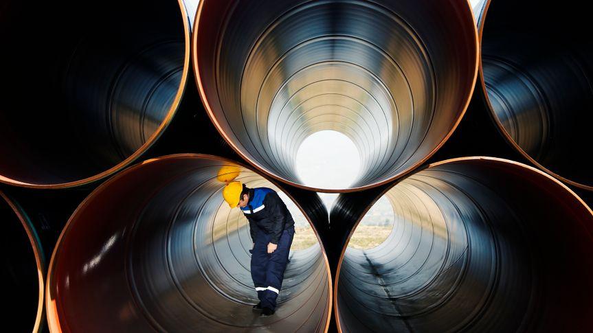 steel worker walking in steel pipe