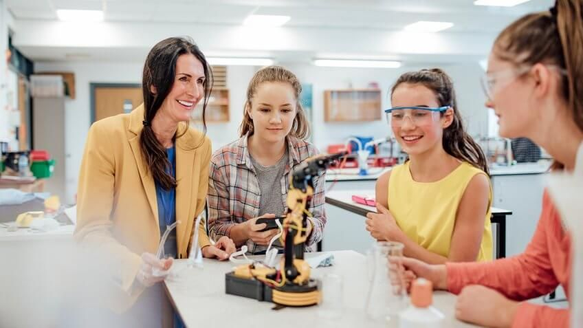 Point of view angle of teenage girls studying robotic arm in school.
