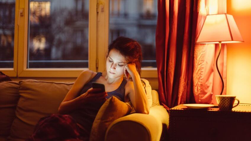 Unhappy woman at home text messaging.