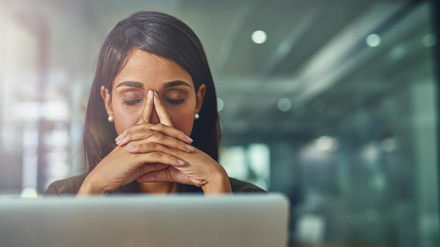 Shot of a young businesswoman looking stressed out while working in an office.