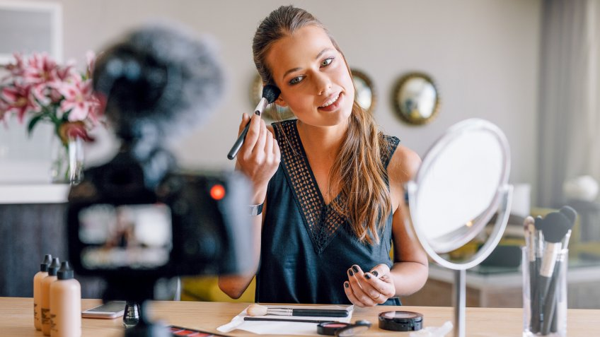 woman doing make-up for video blog