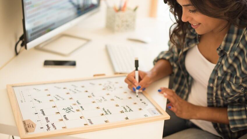 woman making notes in calendar
