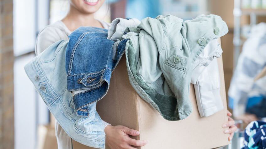 woman holds a box of gently used clothing