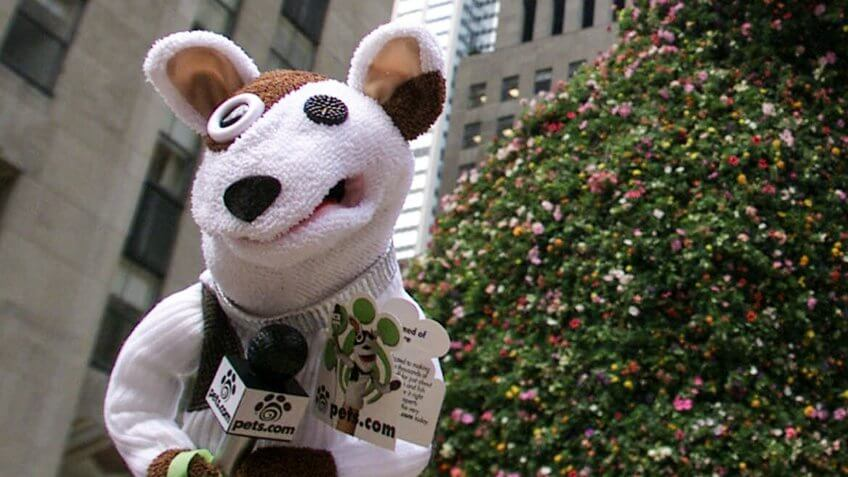 "The Pets.com Sock Puppet makes an appearance near Jeff Koons' ""Puppy"" in Rockefeller Plaza"