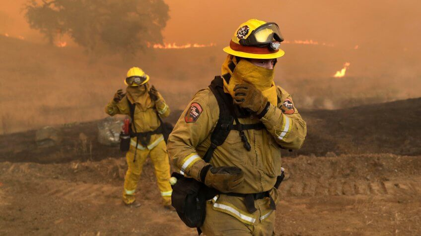 Mandatory Credit: Photo by Marcio Jose Sanchez/AP/REX/Shutterstock (9774405g)Firefighters with Cal Fire Mendocino Unit cover themselves from smoke and ash created by an advancing wildfire, in Lakeport, Calif.