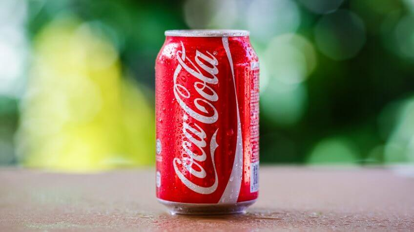 SABAH, MALAYSIA April 10, 2015 : Coca-Cola Can with background blurring tree in a park.