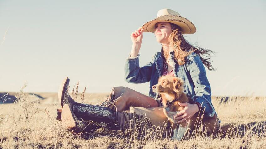 A cowgirl sitting on a grassy prairie