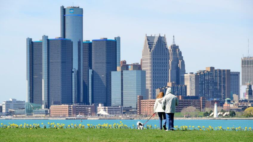 """Detroit, Michigan, USA - April 4, 2012: People walking their dog on a sunny day on Belle Isle, a city park in the Detroit River."