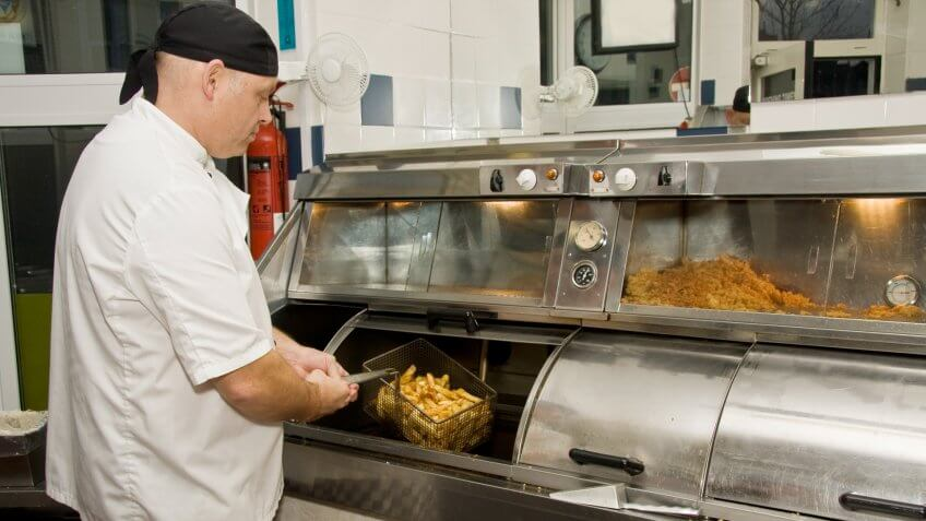 """Interior of a British fish and chip shop, showing a cook removing chips from the fryer."