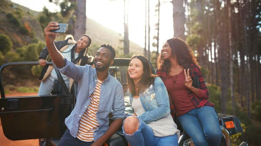 Young friends with camera phone taking selfie at jeep in woods.